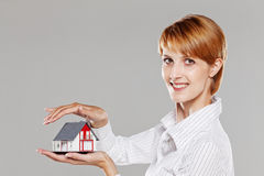 Female hands sheltering a model house Stock Image