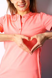 Female hands show heart Valentine`s. Female hands show heart of palets, on a pink shirt. Valentine`s Day Concept royalty free stock image