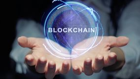 Hands show round hologram Blockchain. Female hands show a round conceptual hologram with text Blockchain. Unrecognizable woman in ashen white on a black stock video footage