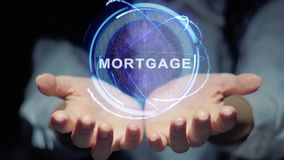 Hands show round hologram Mortgage. Female hands show a round conceptual hologram with text Mortgage. Unrecognizable woman in ashen white on a black background stock footage