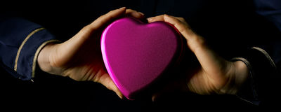 Female hands showing heart shaped candy box. Black Mania. female hands isolated on black background showing heart shaped candy box stock photos