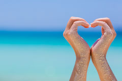 Female hands showing heart sympbol on sea background. Female hands showing heart sympbol on blue sky and sea background stock images