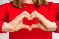 Female hands showing sign of heart on red. Jumper stock images