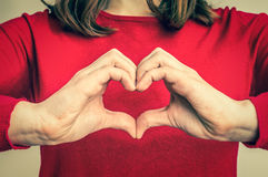 Female hands showing sign of heart - retro style. Female hands showing sign of heart on red jumper - retro style royalty free stock photos
