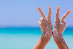 Female hands showing victory sympbol on sea background. Female hands showing victory sympbol on blue sky and sea background Royalty Free Stock Photography