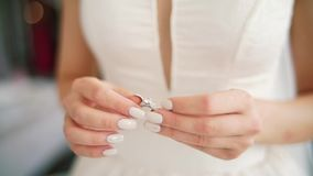 Female hands with silver golden ring diamond rack focus. Woman wear engagement wedding ring on finger polished nails. Lace dress worry before ceremony. close up stock video