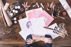 Female hands and sketches with paints at artist workplace stock photography