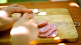 Female hands sliced sausage on a wooden cutting stock video
