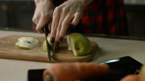 Female hands slicing apple on cutting board. Female hands with perfect manicure slicing green apple with knife on wooden cutting board in the kitchen. Closeup stock video footage