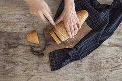 Female hands slicing bread. On wooden table Stock Photo