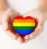 Female hands with small rainbow heart. Gay pride, homosexual, love and charity concept - close up of female hands holding small rainbow heart royalty free stock image