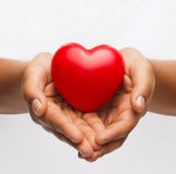 Female hands with small red heart. Health, medicine and charity concept - close up of african american female hands with small red heart royalty free stock images