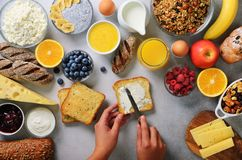 Female hands spreading butter on bread. Woman cooking breakfast. Healthy breakfast ingredients, food frame. Granola, egg stock image
