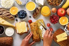 Female hands spreading butter on bread. Woman cooking breakfast. Healthy breakfast ingredients, food frame. Granola, egg stock images