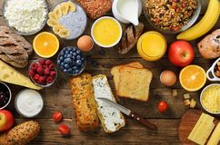 Female hands spreading butter on bread. Woman cooking breakfast. Healthy breakfast ingredients, food frame. Granola, egg royalty free stock photo