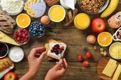 Female hands spreading butter and jam on bread. Woman cooking breakfast. Healthy breakfast ingredients, food frame stock image