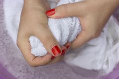 Female hands squeeze white clothes close-up stock photos