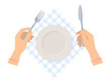 Female hands with steel fork and knife and empty plate. Stock Photo