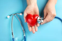Female hands with stethoscope and small heart on color background royalty free stock image