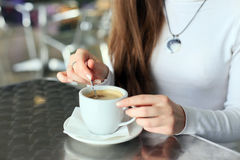 Female hands stirred the coffee in the cup Stock Image