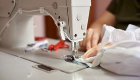 Female hands at sewing process and repairing white fabric on professional manufacturing machine. Close up view. Female hands stitching white fabric on stock image