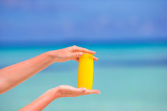 Female hands with suncream bottle background blue Royalty Free Stock Photography