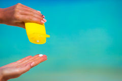 Female hands with suncream bottle background blue Royalty Free Stock Image