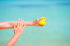 Female hands with suncream bottle background blue Royalty Free Stock Photo