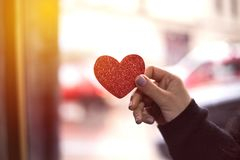 Female hands take heart, Happy Valentine& x27;s Day. stock image