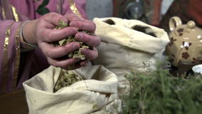 Female hands take herbs from the sack and slowly throw it back stock video footage