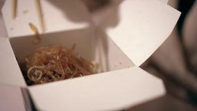 Female hands take noodles out of the box using chopsticks.