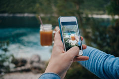 Female hands take pictures of orange juice for a social network Stock Photos