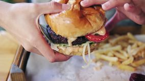 Female hands taking big tasty burger from a wooden tray and getting ready to eat it. Slowmotion shot.  stock video