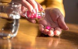 Female hands taking medication, hard light. Close up of female hands taking medication, hard light stock images