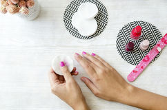 Female hands taking off nail polish from nails on wooden table. Top view Stock Image