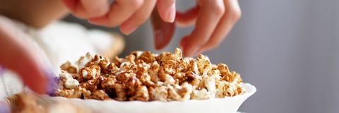 Female hands taking popcorn grains out from bowl while watching tv royalty free stock photos