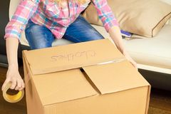 Female hands taping a box. Person using adhesive tape, relocation. Time saving tips for moving Stock Photos