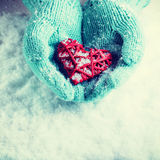 Female hands in teal knitted mittens with a entwined vintage romantic heart on a snow background. Love and St. Valentine concept Royalty Free Stock Photo
