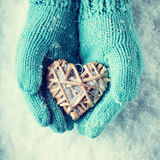 Female hands in teal knitted mittens with a entwined vintage romantic heart on a snow background. Love and St. Valentine concept Royalty Free Stock Photos