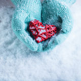 Female hands in teal knitted mittens with a entwined vintage romantic heart on a snow background. Love and St. Valentine concept Stock Photos