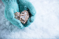Female hands in teal knitted mittens with a entwined vintage romantic heart on a snow background. Love and St. Valentine concept Stock Photography