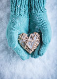 Female hands in teal knitted mittens with a entwined vintage romantic heart on a snow background. Love and St. Valentine concept Stock Images