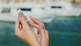 Female hands with telephone on a background of a blurry plan with the sea and yachts. Always connected, even on vacation.  stock video