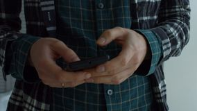 Female hands texting message on mobile phone. Midsection of young woman networking online , typing text message on mobile phone while standing near window in stock footage