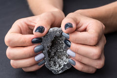 Female hands with textured silver mineral Royalty Free Stock Photos