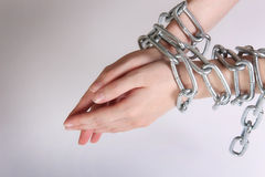 Female hands tied by chain Stock Image