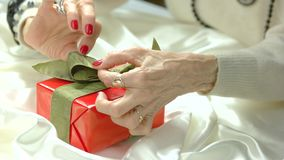 Female hands tied red green bow on gift box. Old woman manicured hands wrapped beautiful box with gift. Holidays and celebrations concept stock video footage