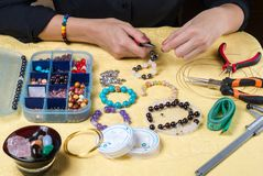Female hands with a tool and colorful beads royalty free stock photography