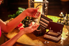Female hands touch bead decorations. Stock Photography