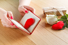 Female hands touch red heart on diary for Valentine's day with g Royalty Free Stock Image